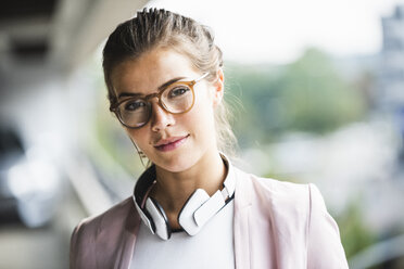 Portrait of a young businesswoman with headphones around her neck - UUF15614