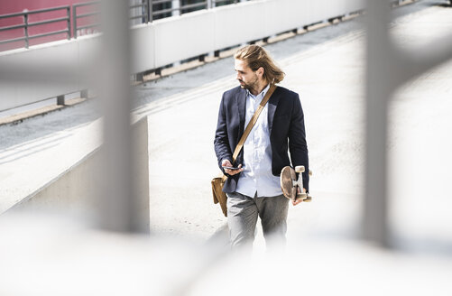 Young businessman carrying skateboard, using smartphone - UUF15620