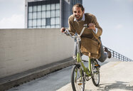 Laughing businessman riding down a ramp on his bicycle - UUF15629