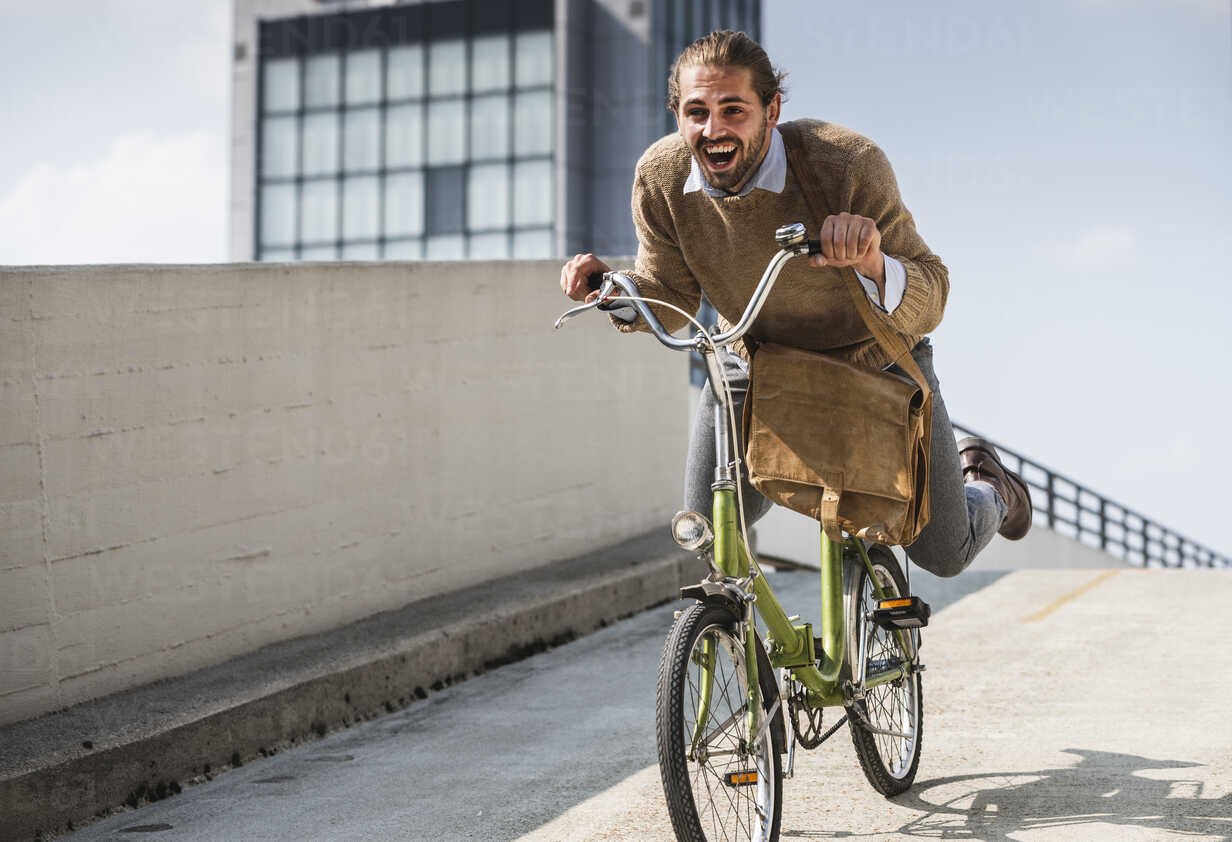 Laughing businessman riding down a ramp on his bicycle - UUF15629 - Uwe Umstätter/Westend61