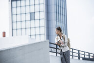 Young businesswoman leaning on railing, waiting in the city - UUF15632