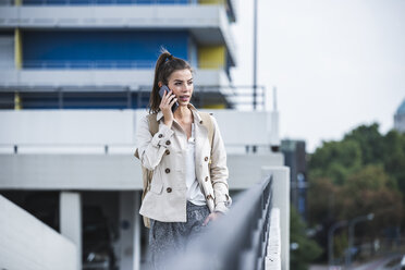 Young businesswoman using smartphone in he city - UUF15635