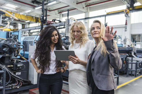 Three women with tablet talking in factory shop floor - DIGF05282