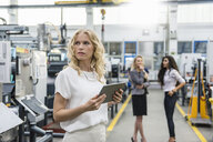 Woman holding tablet in factory shop floor with two women in background - DIGF05285
