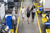 Three women with tablet walking and talking in factory shop floor - DIGF05291