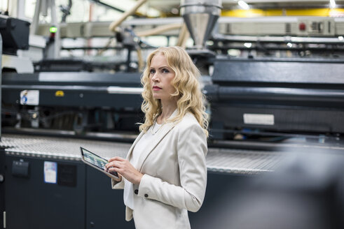 Woman with tablet at machine in factory shop floor looking around - DIGF05297