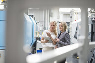 Two women with tablet talking in factory shop floor - DIGF05312