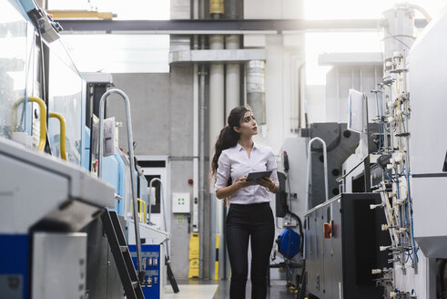 Woman with tablet at machine in factory shop floor lookig around - DIGF05318