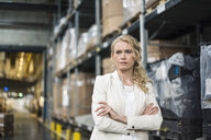 Portrait of confident woman in factory storehouse - DIGF05324