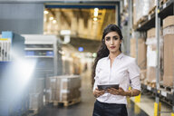 Portrait of woman holding tablet in factory storehouse - DIGF05327