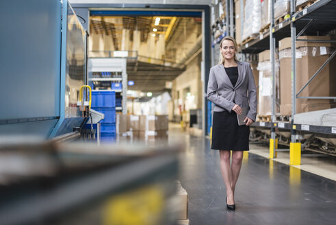 Portrait of smiling woman with tablet standing in factory storehouse - DIGF05330