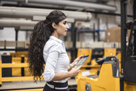 Woman holding tablet in factory shop floor - DIGF05348