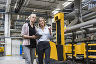 Two women with tablet walking and talking in factory shop floor - DIGF05357