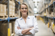 Portrait of smiling woman in factory storehouse - DIGF05363