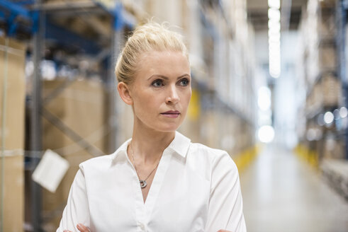 Portrait of confident woman in factory storehouse - DIGF05372