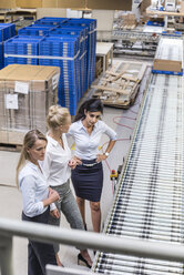Three women discussing at conveyor belt in factory - DIGF05375