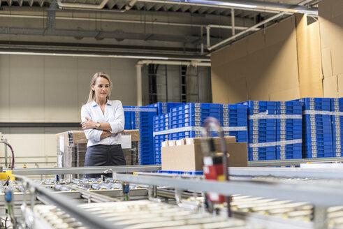 Woman looking at conveyor belt in factory - DIGF05378