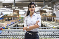Portrait of confident woman at conveyor belt in factory - DIGF05381