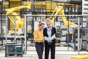 Two women discussing plan in factory shop floor with industrial robot - DIGF05387