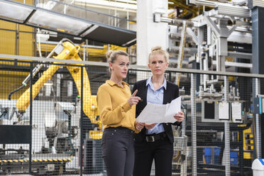 Two women discussing plan in factory shop floor with industrial robot - DIGF05390