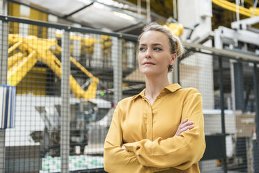 Portrait of confident woman in factory shop floor with industrial robot - DIGF05393