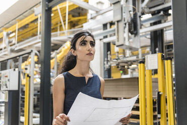 Woman holding plan in factory shop floor with industrial robot - DIGF05396