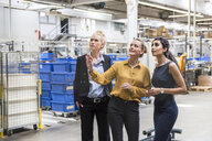 Three women talking in modern factory - DIGF05399