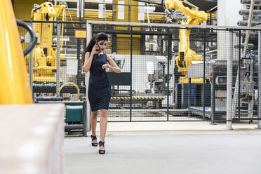 Woman on the phone walking in factory shop floor with industrial robot checking the time - DIGF05408