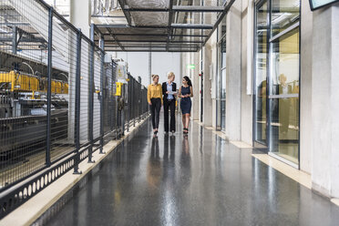 Three women with tablet walking and talking in factory shop floor - DIGF05411