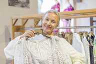Portrait of smiling senior woman shopping for clothes in a boutique - VGF00021