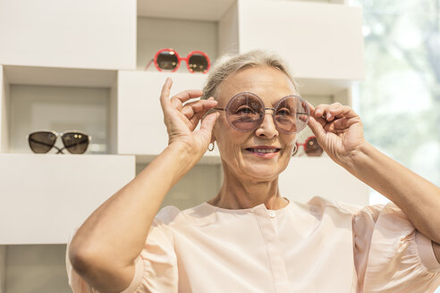 Smiling senior woman trying on sunglasses in a boutique - VGF00030