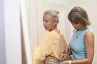 Shop assistant helping senior woman in a boutique - VGF00033