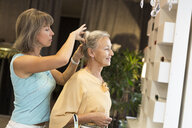 Woman helping senior woman with her hair in a shop - VGF00036
