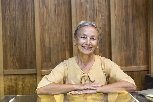 Portrait of smiling senior woman at reception - VGF00042
