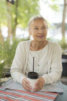 Smiling senior woman at an outdoor cafe looking sideways - VGF00045