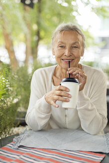Portrait of smiling senior woman at an outdoor cafe - VGF00048
