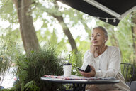 Senior woman at an outdoor cafe with cell phone and earphones - VGF00057