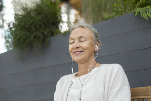 Smiling senior woman with closed eyes wearing earphones outdoors - VGF00060
