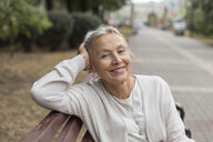 Portrait of smiling senior woman relaxing on a bench - VGF00063