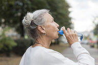 Senior woman outdoors drinking water from bottle - VGF00066