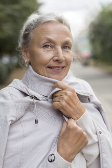 Portrait of smiling senior woman wearing a coat - VGF00069