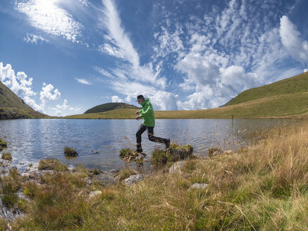 Italy, Lombardy, hiker jumping at lakeside - LAF02102