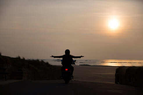 Silhouette of young couple on motorcycle at sunset - LUXF01669