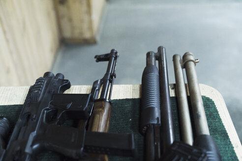 Assortment of rifles on table in an indoor shooting range - KKAF02581