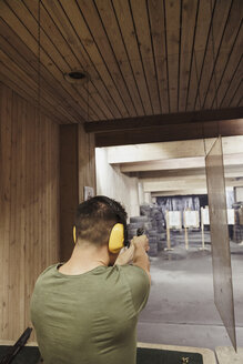 Man aiming with a pistol in an indoor shooting range - KKAF02584