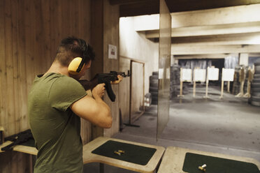 Man aiming with a rifle in an indoor shooting range - KKAF02587
