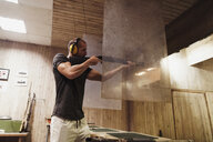 Man aiming with a rifle in an indoor shooting range - KKAF02590