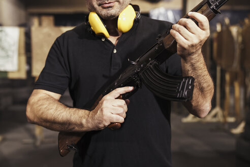 Close-up of man holding a rifle in an indoor shooting range - KKAF02593