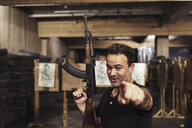 Portrait of man with a rifle pointing his finger in an indoor shooting range - KKAF02596