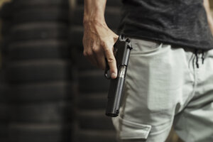 Close-up of man holding a pistol - KKAF02599
